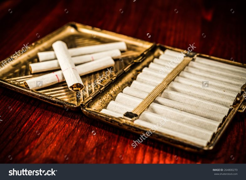 stock-photo-old-cigarette-case-with-cigarettes-on-a-table-in-mahogany-image-vignetting-264800270